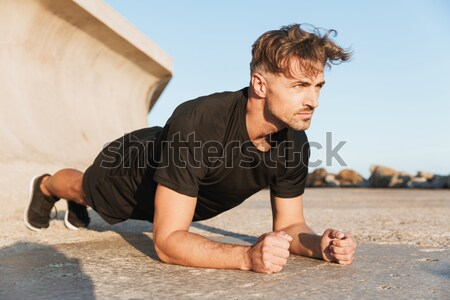 Portrait of an injured sportsman suffering from knee pain Stock photo © deandrobot