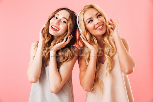 Image of Two pleased pretty women in pajamas having fun Stock photo © deandrobot