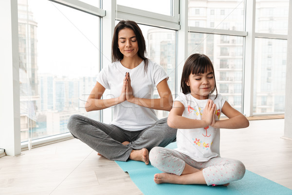 Beautiful mother and child meditating at home, sitting legs cros Stock photo © deandrobot