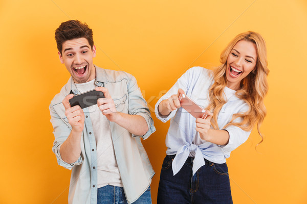 Image of cheerful man and woman playing together video games on  Stock photo © deandrobot