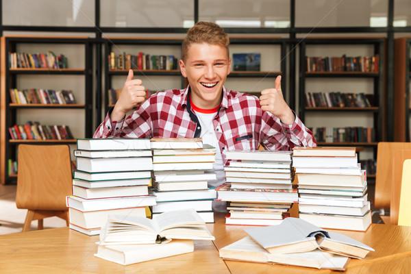 Mosolyog tizenéves fiú ül könyvtár asztal nagy Stock fotó © deandrobot