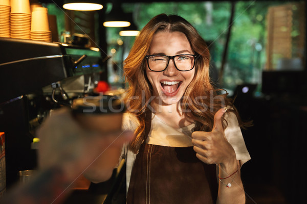 Portrait of a happy young barista girl in apron Stock photo © deandrobot