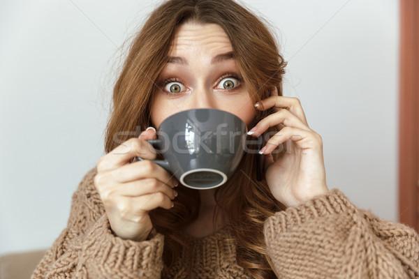 Fotó derűs fiatal nő 20-as évek néz kamera Stock fotó © deandrobot