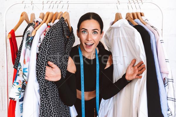 Izgatott fiatal nő ruházat designer áll ruhaakasztó Stock fotó © deandrobot