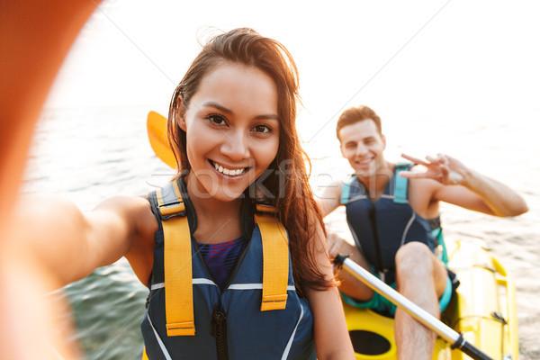 Loving couple kayaking on lake sea in boat make selfie by camera. Stock photo © deandrobot