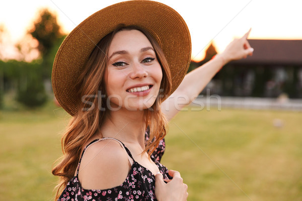 Photo of joyous pretty woman wearing straw hat smiling, and walk Stock photo © deandrobot