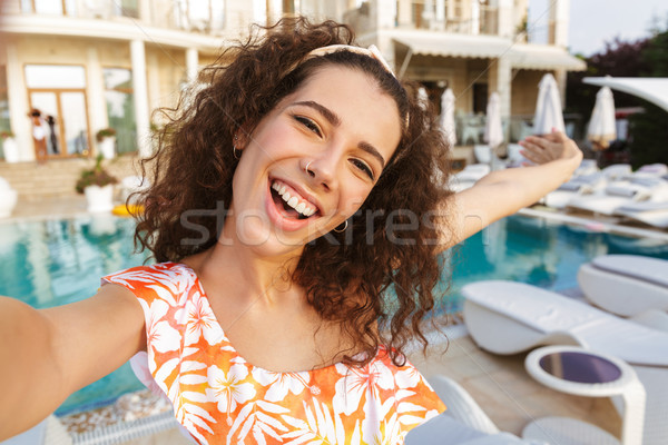Happy young woman in swimsuit taking a selfie Stock photo © deandrobot