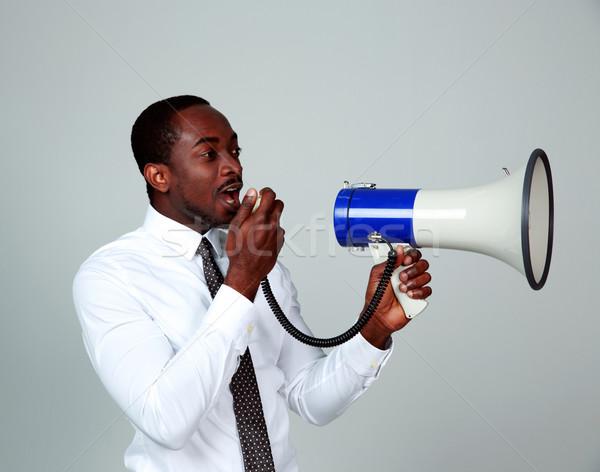 Africano homem megafone cinza notícia Foto stock © deandrobot