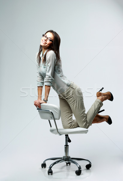 Young happy businesswoman having fun on office chair on gray background Stock photo © deandrobot