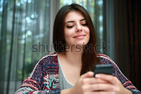 Serious beautiful woman using smartphone at home Stock photo © deandrobot