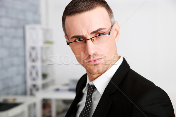 Portrait of a confident businessman in glasses at office Stock photo © deandrobot