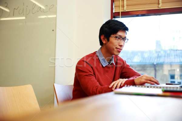 Young asian student in glasses sitting at the table Stock photo © deandrobot