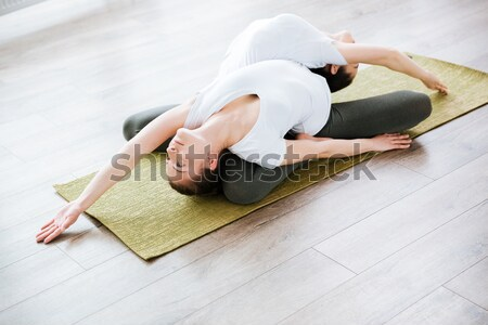 Young woman in sport cloths lying on the yoga mat Stock photo © deandrobot