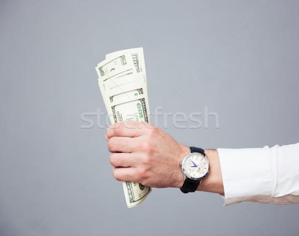 Businessman hand holding bills of US dollar Stock photo © deandrobot