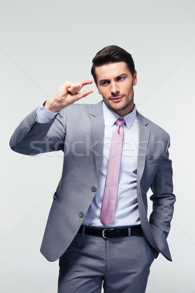 Businessman showing size with fingers Stock photo © deandrobot
