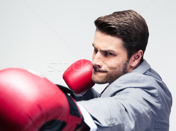 Businessman in boxing gloves hitting at camera Stock photo © deandrobot