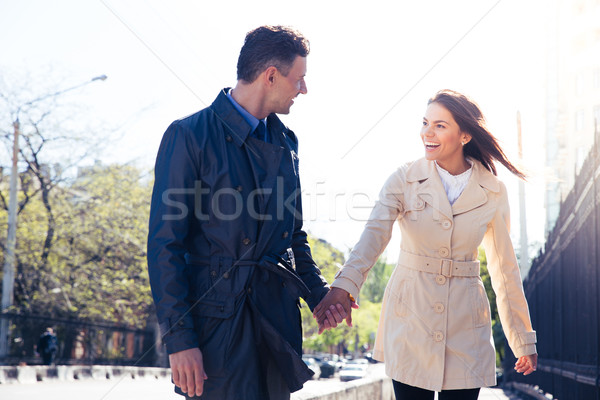 Laughing couple walking outdoors Stock photo © deandrobot