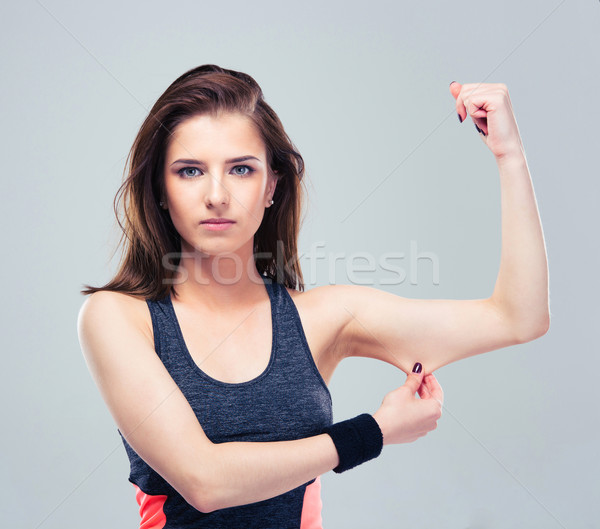 Fitness woman pinch a fat on her biceps Stock photo © deandrobot