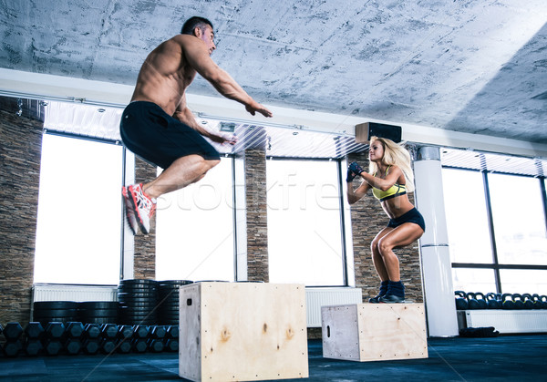 Man and woman jumping on fit box Stock photo © deandrobot