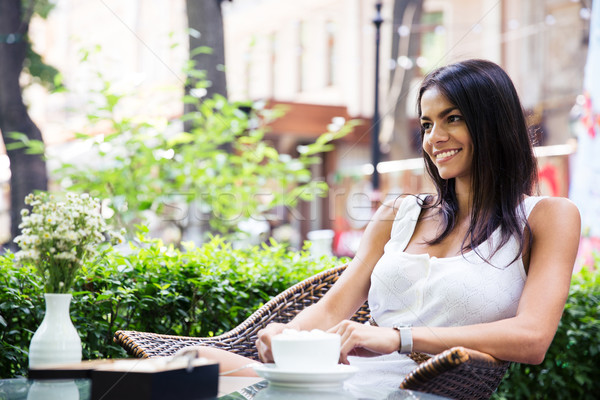 Happy young woman sitting in outdoors cafe Stock photo © deandrobot