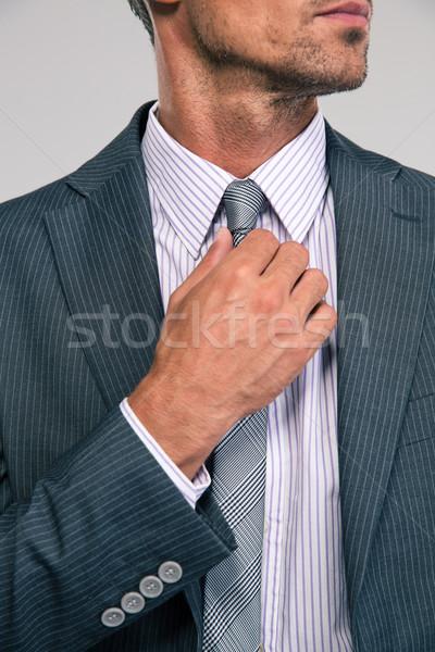 Businessman straightening his tie Stock photo © deandrobot