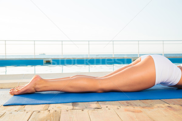 Woman lying on yoga mat  Stock photo © deandrobot
