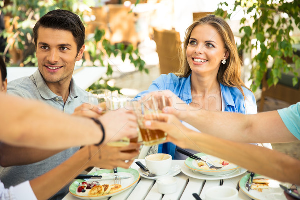 Friends making toast around table Stock photo © deandrobot