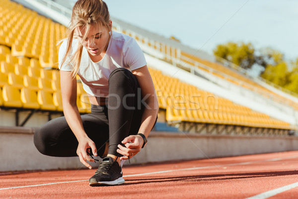 Woman tie shoelaces at outdoor stadium Stock photo © deandrobot