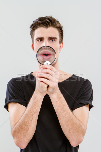 Handsome carismatic man using magnifying glass Stock photo © deandrobot