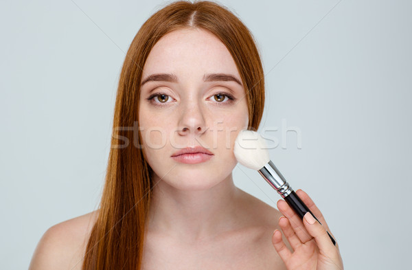 Redhair woman using makeup brush Stock photo © deandrobot