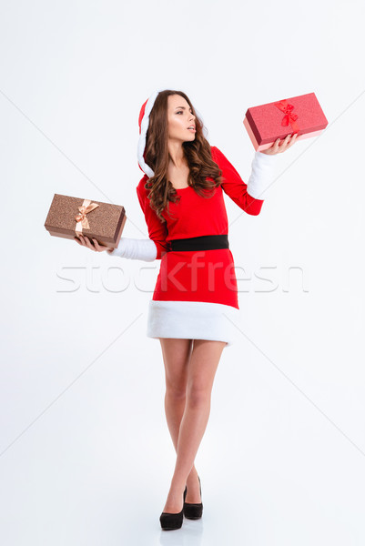 Thoughtful woman in santa claus cloth holding two gift boxes Stock photo © deandrobot