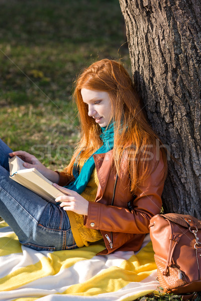 Concentrated smart girl reading a book under the tree Stock photo © deandrobot