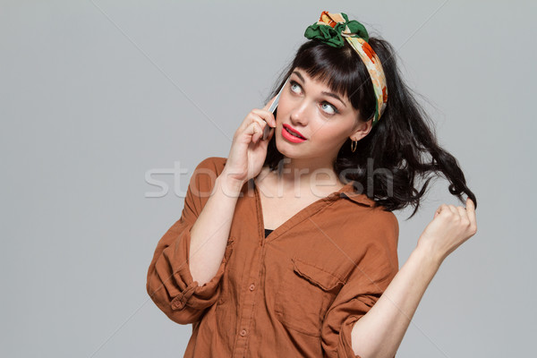 Pretty pensive young woman talking on mobile phone isolated  Stock photo © deandrobot
