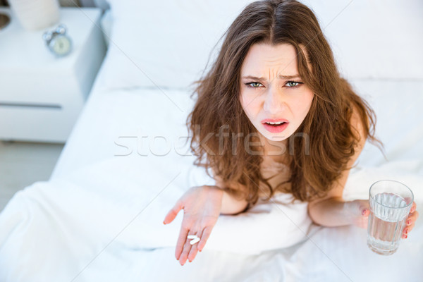 Woman sitting on bed with pills and glass of water  Stock photo © deandrobot