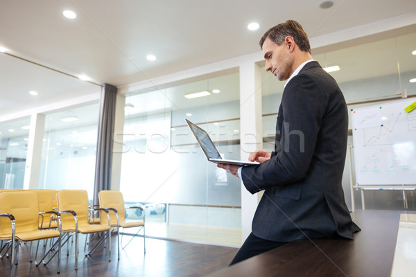Focused serious businessman preparing for presentation using laptop  Stock photo © deandrobot