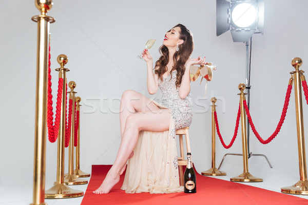 Woman holding heels and glass of champagne  Stock photo © deandrobot