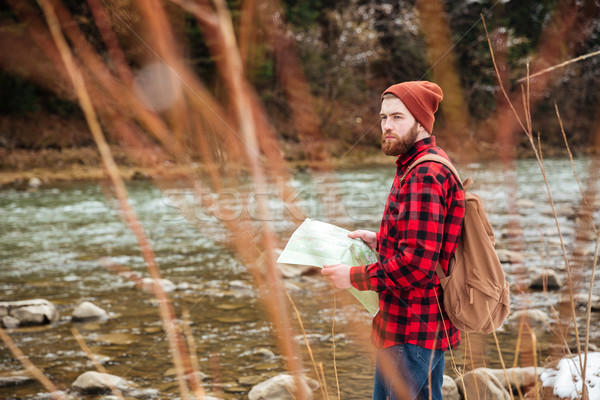 Male hiker holding map and looking away outdoors  Stock photo © deandrobot