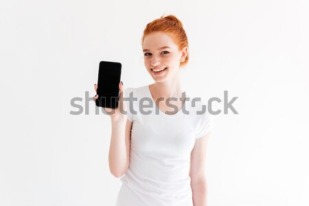 Happy woman listening to misuc from blank screen smartphone Stock photo © deandrobot