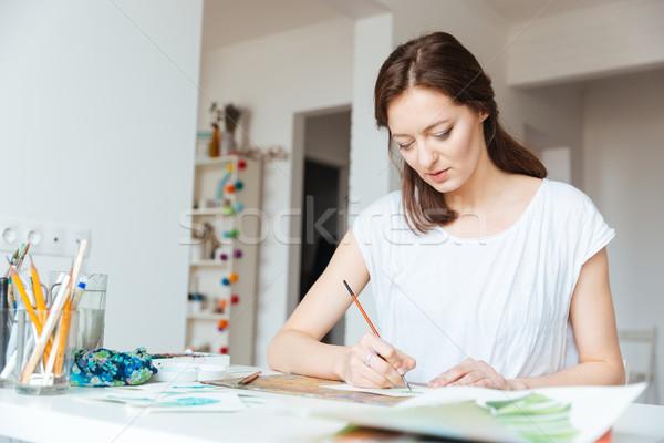 Beautiful inspired woman painter painting in art studio Stock photo © deandrobot