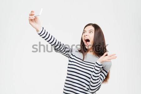 Cheerful woman with mouth open looking at camera Stock photo © deandrobot
