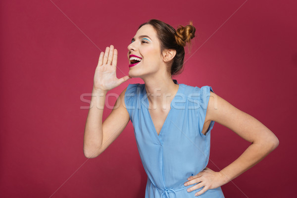 Cheerful cute young woman shouting and calling for somebody  Stock photo © deandrobot