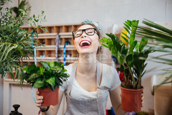 Happy woman florist holding plants in flowerpots and laughing  Stock photo © deandrobot