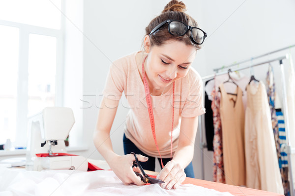 Smiling woman seamstress cutting white fabric with scissors Stock photo © deandrobot