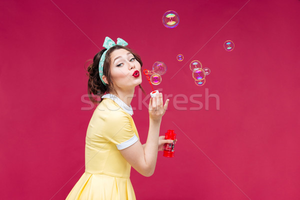 Playful cute pinup girl in yellow dress blowing soap bubbles Stock photo © deandrobot