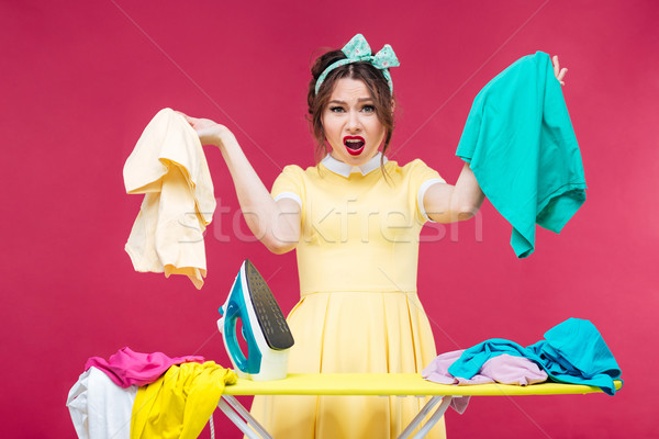 Disappointed angry woman holding clothes and shouting near ironi Stock photo © deandrobot