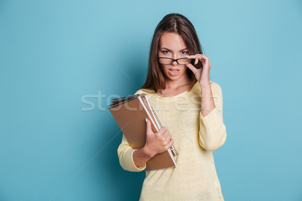 Smart beautiful woman looking at camera and touching glasses Stock photo © deandrobot