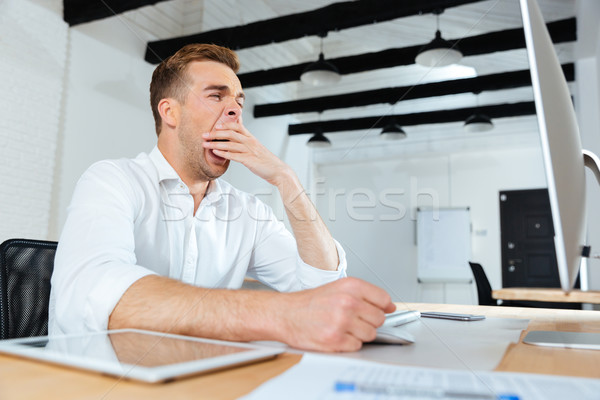 Sleepy tired young businessman working and yawning Stock photo © deandrobot