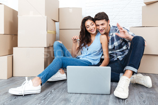 Happy couple sitting on floor moving in a new house Stock photo © deandrobot