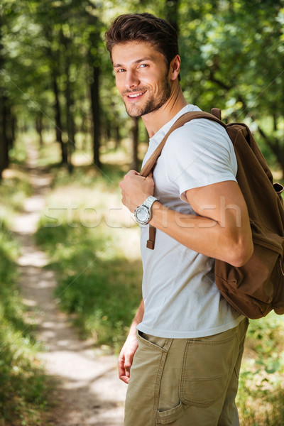 Man holding backpack and walking in forest Stock photo © deandrobot