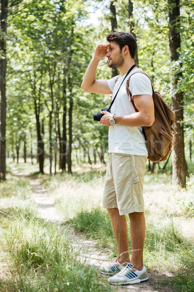 Man photographer using camera and looking far away in forest Stock photo © deandrobot